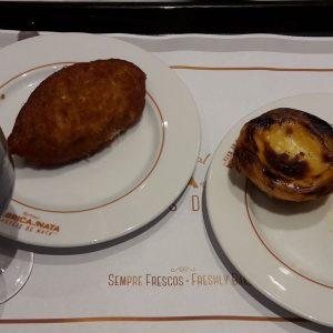Una tavola imbandita con ciò che puoi ordinare in una pastelaria: un calice di vino, un pastel de bacalhau e du pastel de nata